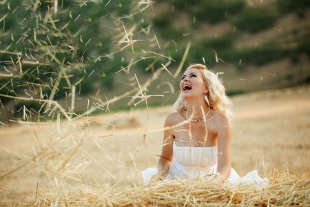 Happy bride playing with hey in field at her wedding day photo