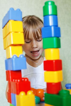 Cute child playing with the constructor bricks at home photo