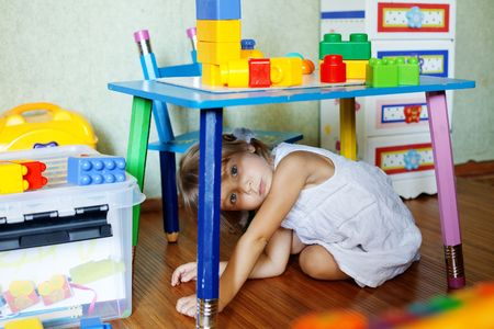little table: Playful child in her nursery at home Stock Photo