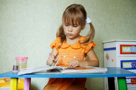 assiduous: Cute girl draw diligently at home Stock Photo