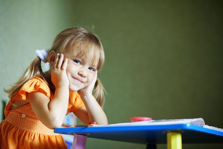 Lovely child sitting at table looking at camera and smiles Stock Photo - 5524758