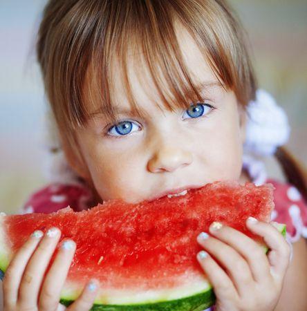 Funny child eating watermelon closeup photo