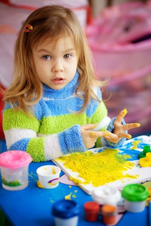 nursery room: Little girl painting in her nursery at home