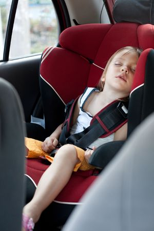 Sleeping child in auto baby seat in car photo
