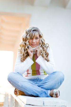 Beautiful blond student girl sitting outdoors Stock Photo