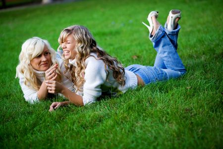 Teenage girls lying together in fresh grass outdoors. photo