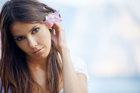 Closeup portrait of beautiful brunette woman with lily in her hair posing over sea photo