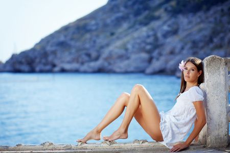 Portrait of beautiful brunette woman with long legs posing over sea view photo