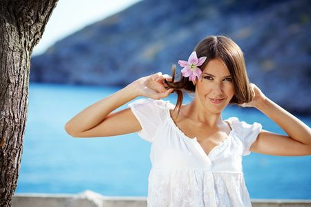 Portrait of beautiful brunette woman with lily in her hair posing over sea view Stock Photo - 5564078