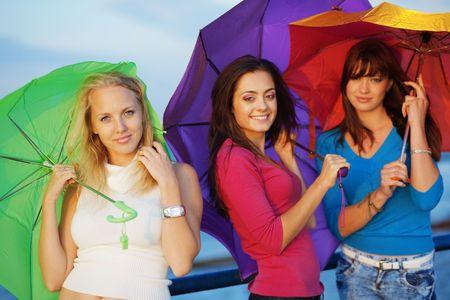 Three fashion teenage girls posing with colorful umbrellas photo