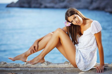 sunbathing: Portrait of beautiful brunette woman with long legs posing over sea view