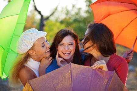 Three fashion teenage girls posing with colorful umbrellas in autumn park photo