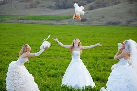 Three happy brides with teddy bears posing on fresh green grass photo