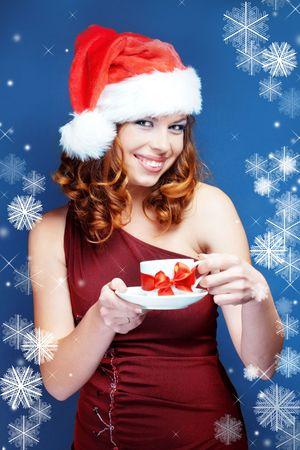 Cute happy Santa helper girl posing on blue studio background with snowflakes photo