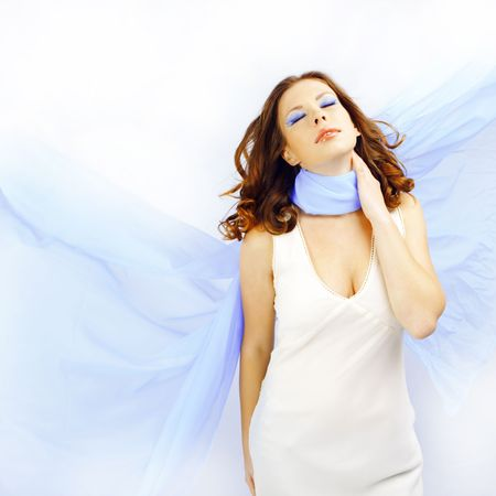 Sensual portrait of beautiful woman with flying blue scarf on white studio background photo