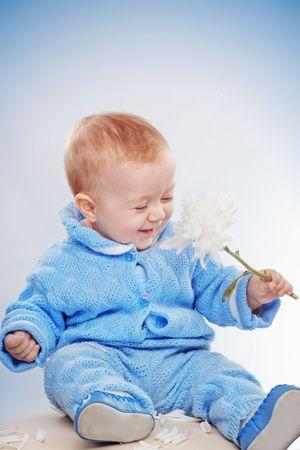 Studio portrait of happy smiling child smelling flower photo