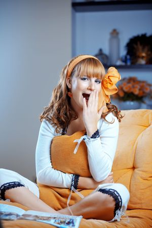 Portrait of cute pin-up housewife resting on sofa at home photo