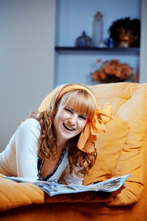 Portrait of cute pin-up housewife reading on sofa at home Stock Photo