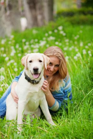 Beautiful woman with playful young dog on fresh green meadow Stock Photo