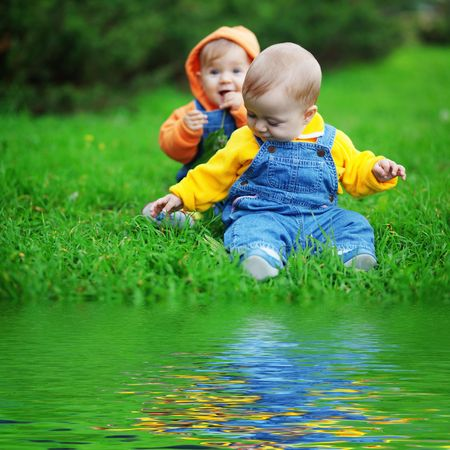 kids playing water: Cute twins babies sitting on fresh green grass in park Stock Photo