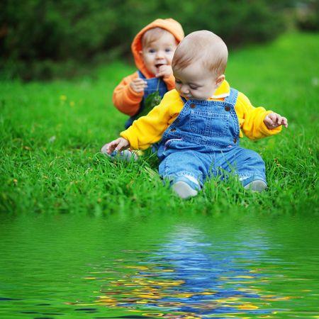 Schattige tweeling babys die op vers groen gras in het park