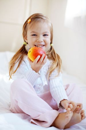 Casual portrait of cute child with apple in bed photo