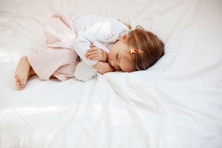 Portrait of child lying in her bed Stock Photo