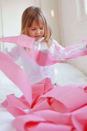 Portrait of child playing with pink toilet paper photo