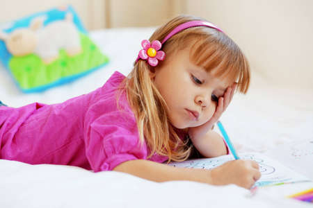 assiduous: Little girl painting in her nursery at home