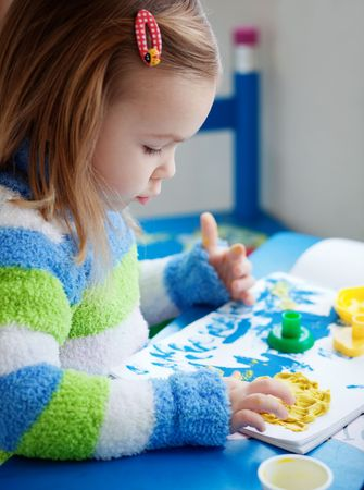 Little girl painting in her nursery at home photo