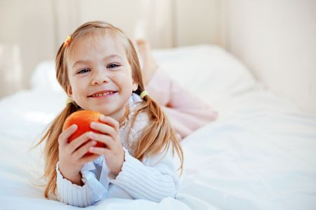 Casual portrait of cute child with apple in bed Stock Photo - 5913017