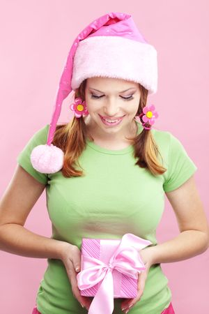 Studio portrait of cheerful cute girl with gift box on pink photo