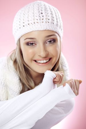 Close-up portrait of beautiful pure young woman wearing white winter clothing photo