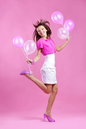 Portrait of cute teenage emotional girl holding balloons on pink studio background photo