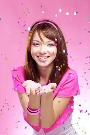 Portrait of young cute girl blowing confetti at holiday party, studio shot Stock Photo