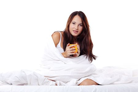 Studio portrait of young beautiful woman on bed holding cup of tea photo