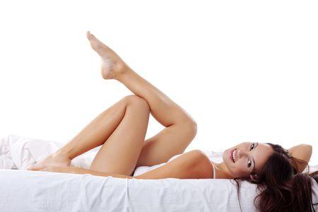 benen: Studio portret van jonge prachtige vrouw op bed