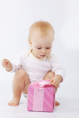 Portrait of child opening gift box in white studio