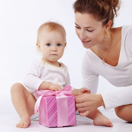 Portrait of mother with her baby opening gift box in white studio photo