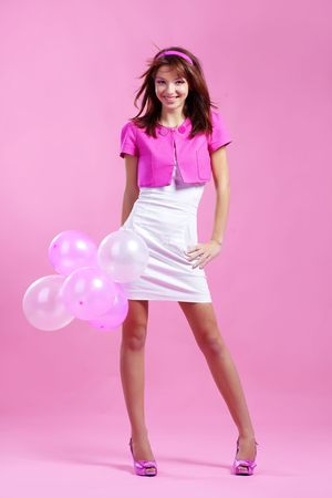 Portrait of cute teenage emotional girl holding balloons on pink studio background Stock Photo - 5992814