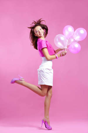 Portrait of cute teenage emotional girl holding balloons on pink studio background