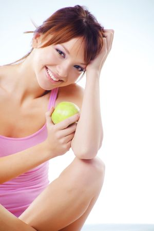 Portrait of cute cheerful teenage girl with green juicy apples