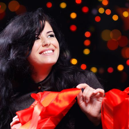 Cute woman with presents at night holiday celebration photo