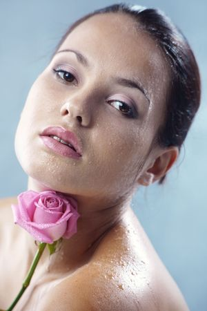 Studio portrait of sensual beautiful woman with rose and water droplets on her face photo