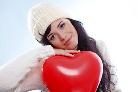 Cute young woman wearing warm winter clothing and holding heart posing in studio Stock Photo - 6018722