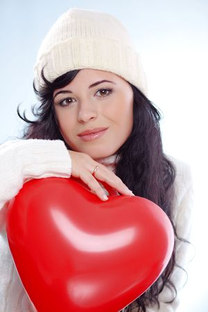 Cute young woman wearing warm winter clothing and holding heart posing in studio photo