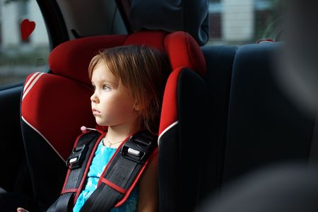 child seat: Child in auto baby seat in car looking at window Stock Photo