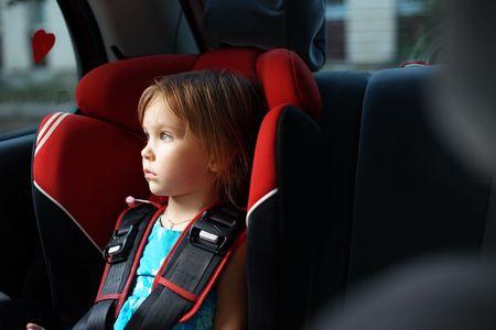 asiento coche: Ni�o en el asiento de beb� de auto en auto mirando la ventana Foto de archivo