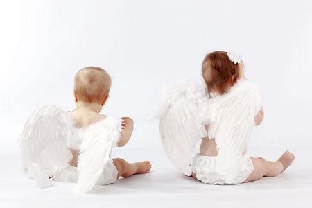 Two cute valentine angel babies sitting back on light studio background Stock Photo