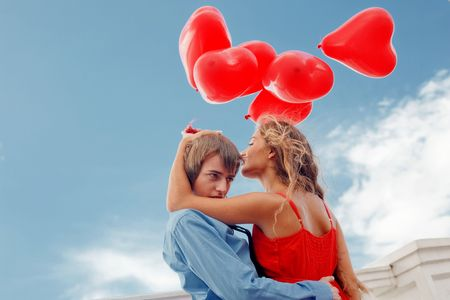 Teenage couple embracing over sky and holding bunch of baloons-hearts photo
